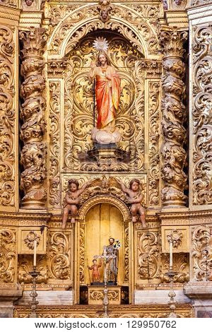 Santarem, Portugal. September 10, 2015: Baroque gilded chapel with a Jesus Christ image inside the Santarem See Cathedral aka Nossa Senhora da Conceicao Church. 17th century Mannerist style.
