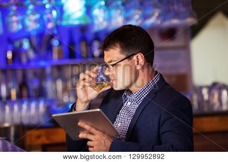 Side view of man in glasses and suit looking at pad while drinking cold drink