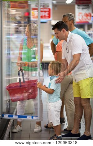 Happy family with child near open fridge in supermarket