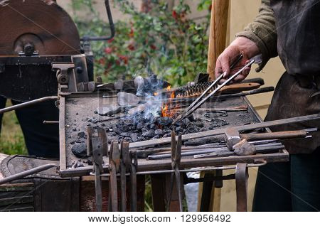 Blacksmith working on metal medieval fire iron hammer work