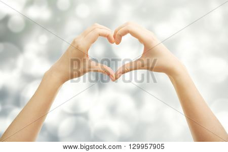 Female hands in shape of heart, on blurred background