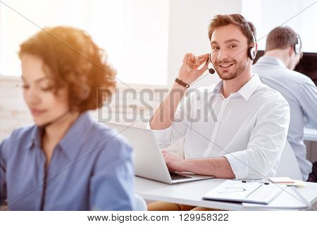 Best worker. Pleasant smiling delighted man sitting at the table and working with his colleagues in the call center while using headset with micro