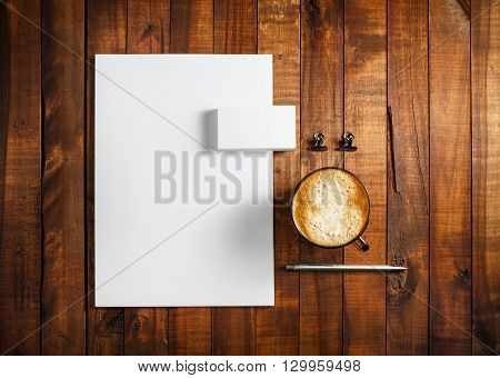 Photo of blank stationery set. Blank corporate identity template on vintage wooden table background. Letterhead business cards coffee cup and pen. Top view.