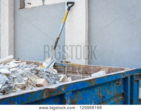Trash construction building demolition waste hard work concept. Spade in pile of rubble. Manual labor tool sticking out from debris.
