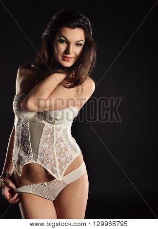 Sexy young woman in white seductive lingerie. photo in dark studio.