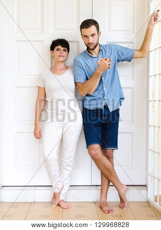 Married couple near them door house. Outdoor photo in sunny day.