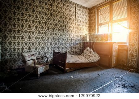 Abandoned Room With Broken Bed, Armchair And Chest Of Drawers To A Dry Aquarium