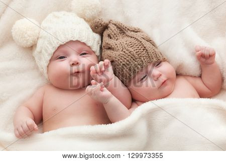 Twin sisters babies lying together wearing funny woolen bobble hats. Happy childhood