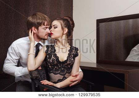 Married couple. Romantic evening at the hotel. Love and passion. Man hugging and kissing his wife