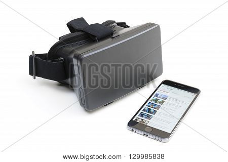 Melbourne, Australia - May 17, 2016: View of a VR headset and an iPhone running newly updated YouTube app with a list of VR videos. This update allows users to watch videos in VR with Google Cardboard