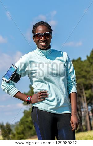 Close up outdoor portrait of young african woman wearing smart watch and smart phone for activity tracking.