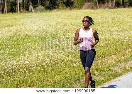 Action shot of young african woman doing exercise in countryside.Teen girl wearing smart phone on arm band and smart watch for activity tracking.