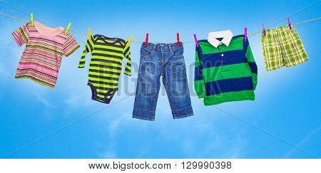 baby clothes on clothesline against blue sky