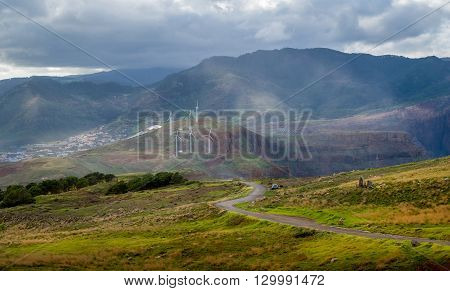 Serpentine road in the beautiful landscape of Madeira island. Fields and hills, wind generators and mountain range view. Canical, Madeira, Portugal.