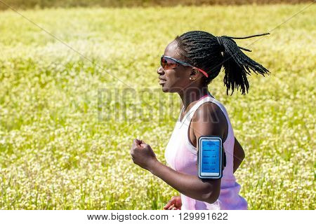 Close up action shot of african teen girl with braided hairstyle jogging against flower field.Woman wearing smart phone on arm band tracking activity.