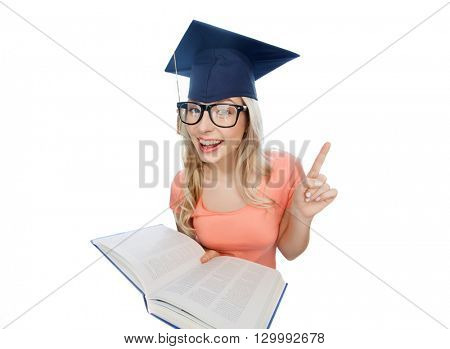 people, education, knowledge and graduation concept - smiling young student woman in mortarboard and eyeglasses with encyclopedia book pointing finger up