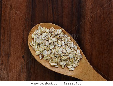 Raw oatmeal in wooden spoon on dark wood table. Flat view of whole oat meal cereal.