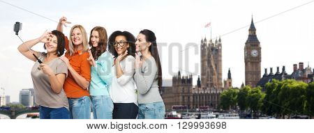 friendship, technology, travel, tourism and people concept - group of happy different size women taking picture with smartphoone on selfie stick over london city and big ben tower background