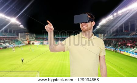 3d technology, virtual reality, sport, entertainment and people concept - happy young man with virtual reality headset or 3d glasses playing game over football field on stadium background