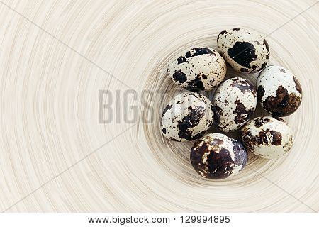 The quail eggs on a wooden board. The rustic still life. The background.