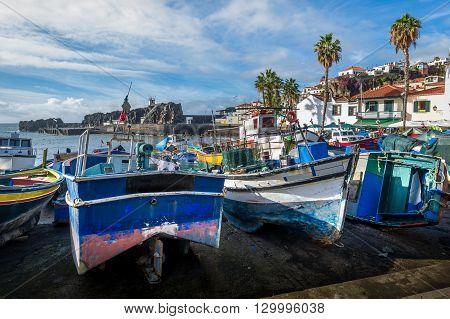 Close view of aged and abandoned fishing boats laying on the shore. Camara de Lobos marina, Madeira, Portugal.