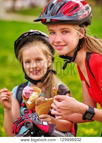Bikes bicyclist girl. Portrait of girls wearing bicycle helmet with rucksack rides bicycle. Girls children are bicycling in summer park. Happy girls biking eating ice cream cone .