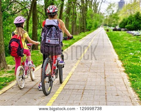 Bikes bicyclist girl. Girls wearing bicycle helmet  with rucksack ciclyng bicycle. Girls children cycling on yellow bike lane. Bike share program save money and time. Back view.