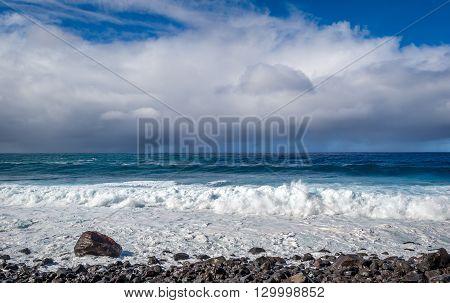 Beautiful Atlantic ocean view with waves splashing to the stone beach and rain clouds on the background. Calhau das Achadas, Madeira island, Portugal.