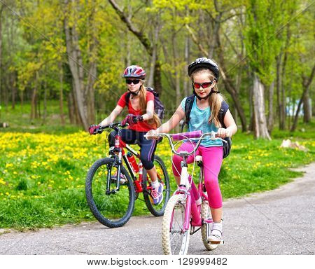 Bikes bicyclist girl. Girls wearing bicycle helmet  with rucksack ciclyng bicycle. Children outrace one another . Bike share program save money and time. Child in foreground  teenager on background.
