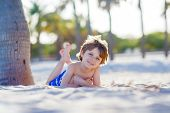 Adorable active little kid boy having fun on Miami beach, Key Biscayne. Happy cute child relaxing and enjoying sunny warm day near palms. poster