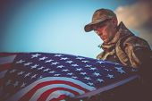 Young Army Veteran with American Flag Closeup Photo. Army Trooper with USA Flag. poster