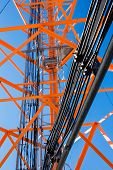 telecommunications tower with feeder cables. orange metal structure tower wire feeder track, stairs, poles. closeup. bottom view poster