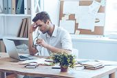 Feeling tired. Frustrated young handsome man looking exhausted while sitting at his working place and carrying his glasses in hand poster