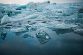 Climate change and global warming. Glacier melting in Iceland. Floating icebergs in Jokulsarlon lagoon. poster