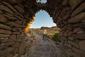 Tourist exploring Inca trails at sunset on Amantani' Island Titicaca Lake among the most scenic travel destination in Peru. Travel adventures and vacations in the Americas. poster