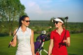 Two smiling sportive women golfers walking on golf course at sunny day poster
