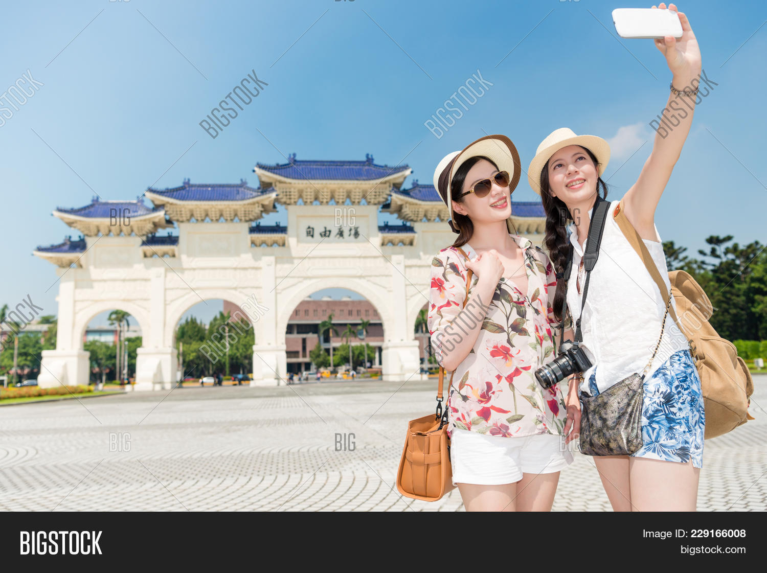 Two Young Asian Ladies Taking A Selfie In The Front Of The Long Historical  Building,