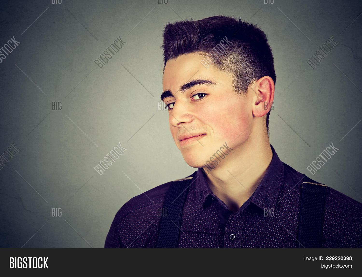 Young Sly Teen Guy Looking At Camera With Expression Of Wily Person On Gray  Background.