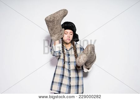 Funny Russian Girl In A Warm Hat With Ear-flaps Holds Warm Felt Boots