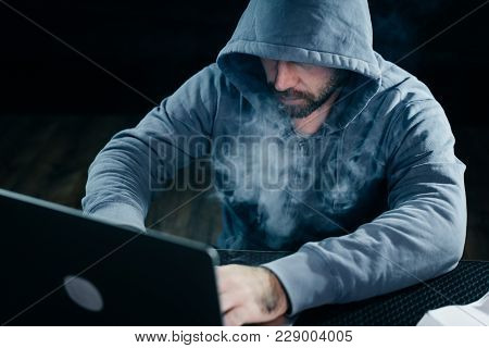 A Criminal Man Hides His Face Under A Hood, Hacks A Laptop, Lots Of Smoke
