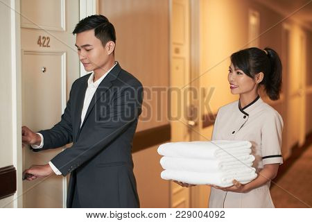 Manager Opening Door For Hotel Maid With Stack Of Towels