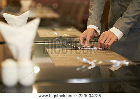 Hands Of Restaurant Manager Putting Silverware On Tables
