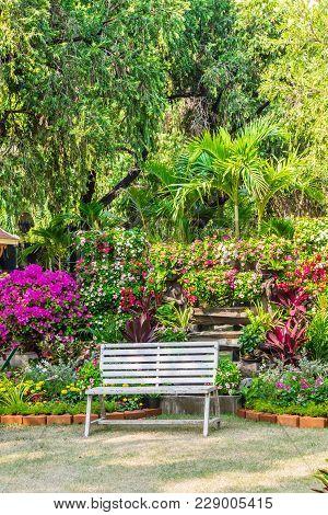 White Chair In Cozy Flower Garden.