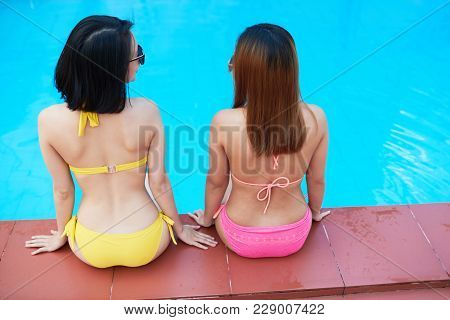 Rear View Of Young Women In Bathing Suits Sitting On The Pool Edge