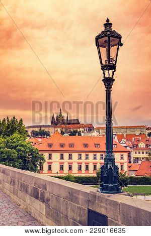 Beautiful evening sunset scenery Of the Old Town and Charles Bridge over Vltava river in Prague, Czech Republic / Old Street Lamp At Sunset On Charles Bridge in Prague