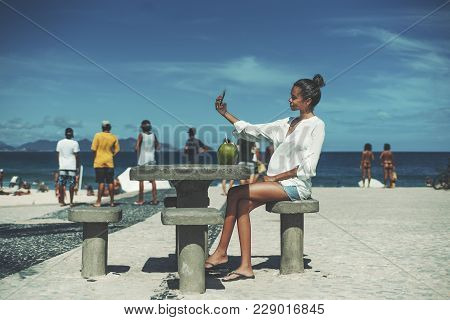 Young Cute Brazilian Female In White Chemise Is Taking Selfie Using Her Cell Phone While Sitting On