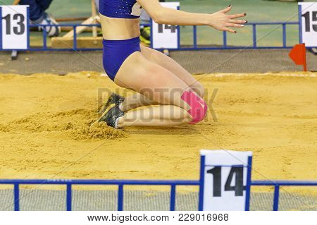 Sportswoman Landing Into Sandpit On Training In Long Jump. Track And Field Competitions Concept Back