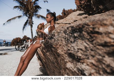 Serious Young Hottie Black Female Is Drinking Fresh Coco Water While Leaning On The Cliff With Beach