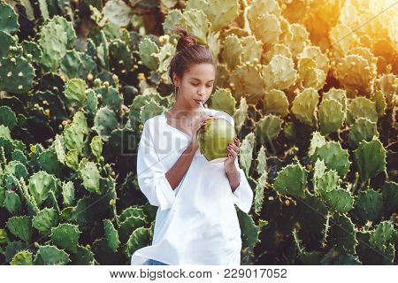 Portrait Of Young Exquisite African American Female Drinking Fresh Coco Water In Front Of Wall Of Ca