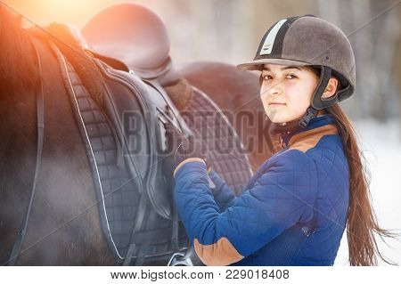 Young Girl Adjusting Stirrups And Saddle Before Riding Her Bay Horse.